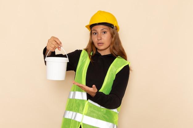 Widok z przodu samica konstruktora w żółtym kasku trzyma farbę stwarzających na białej ścianie kobieta architekt budowy konstruktora