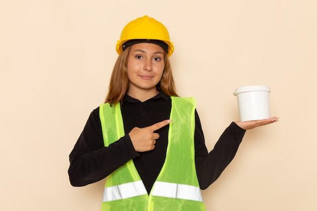 Widok z przodu samica konstruktora w żółtym kasku trzyma farbę z uśmiechem na białej ścianie kobieta architekt budowy konstruktora
