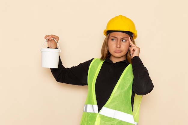 Widok z przodu samica konstruktora w żółtym kasku trzymając farbę i myślenia na białej ścianie kobieta architekt budowy konstruktora