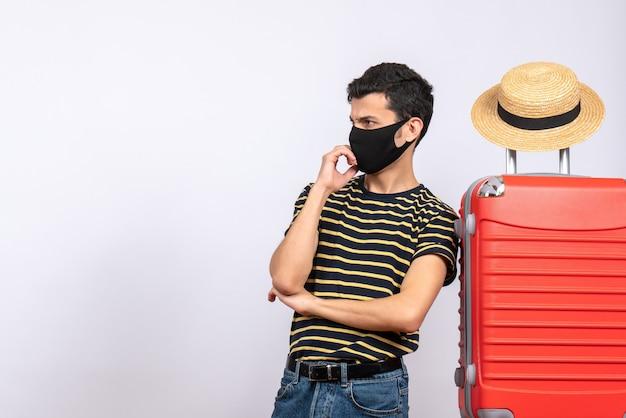 Widok z przodu sceptyczny młody turysta z czarną maską stojący w pobliżu czerwonej walizki