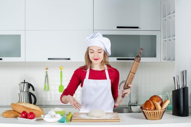 Widok z przodu silna kucharka wskazująca na ciasto na desce do krojenia w kuchni