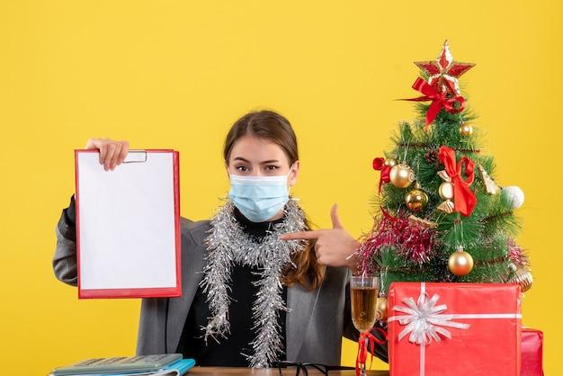 Widok z przodu silna młoda dziewczyna z maską medyczną siedzi przy stole, wskazując palcem jej dokumenty, drzewo boże narodzenie i koktajl prezenty