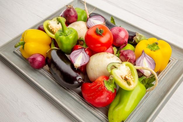 Widok z przodu skład warzyw wewnątrz ramki na białym tle zdjęcie pieprz warzywny dojrzałe zdrowe życie kolor sałatka posiłek