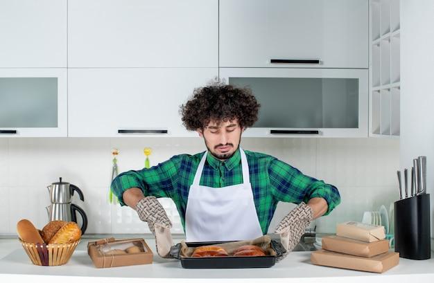 Widok z przodu skoncentrowanego faceta noszącego uchwyt trzymający świeżo upieczone ciasto w białej kuchni