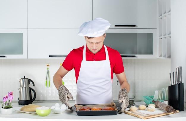 Widok z przodu skoncentrowanego męskiego szefa kuchni noszącego uchwyt trzymający świeżo upieczone ciastka w białej kuchni