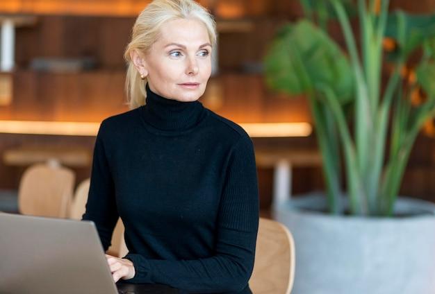 Widok z przodu skoncentrowanej starszej kobiety pracującej na laptopie