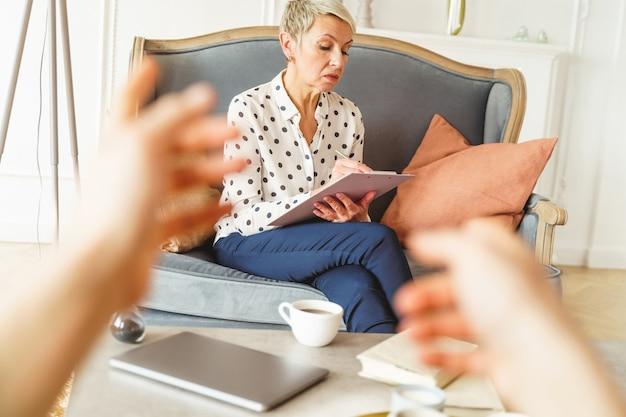 Widok z przodu skoncentrowanej, stylowej, profesjonalnej psychoterapeutki, która robi notatki o swoim kliencie