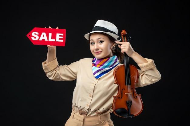 Widok z przodu skrzypaczka trzymająca skrzypce i pisząca sprzedaż na ciemnej ścianie melodia muzyka emocja koncert występ kobieta zakupy grać