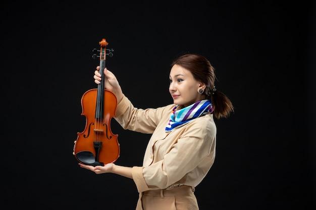 Widok z przodu skrzypaczka trzymająca skrzypce na ciemnej ścianie melodia instrument kobieta występ muzyka emocje koncert gra