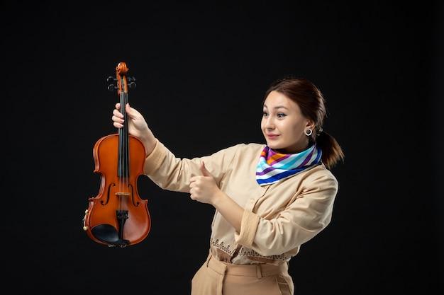 Widok z przodu skrzypaczka trzymająca skrzypce na ciemnej ścianie melodia instrument muzyczny kobieta koncert występ gra emocje