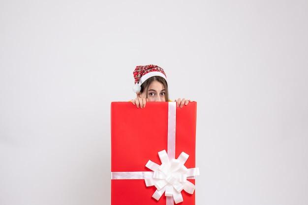 Widok z przodu śliczna dziewczyna z czapką mikołaja chowająca się za wielkim prezentem bożonarodzeniowym