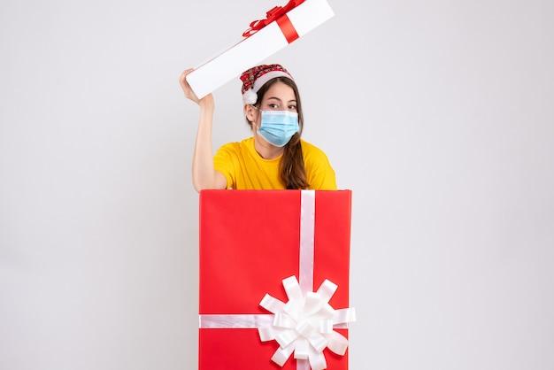 Widok z przodu śliczna dziewczyna z czapką mikołaja i maską medyczną stojąca za wielkim prezentem bożonarodzeniowym