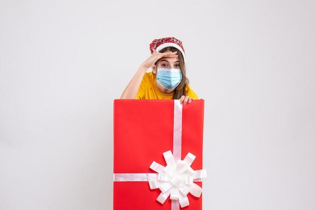 Widok z przodu śliczna dziewczyna z czapką mikołaja kładzie rękę na czole i stoi za wielkim prezentem bożonarodzeniowym