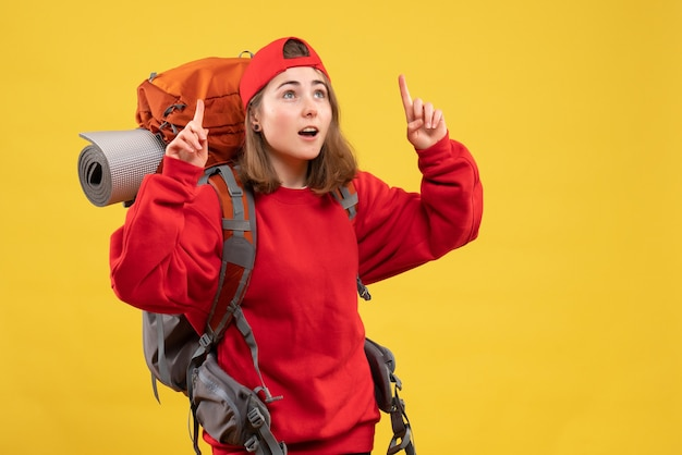 Widok z przodu śliczna podróżniczka z plecakiem wskazująca palcami w górę