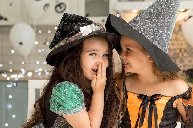 Widok z przodu śliczne dziewczynki z kostiumem czarownicy
