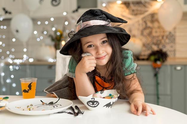 Widok z przodu ślicznej dziewczynki z kostiumem czarownicy