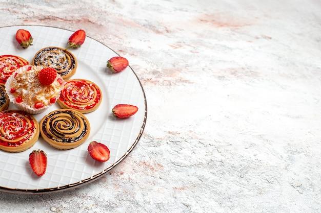 Widok z przodu słodkie ciasteczka okrągłe uformowane wewnątrz talerza na białej przestrzeni