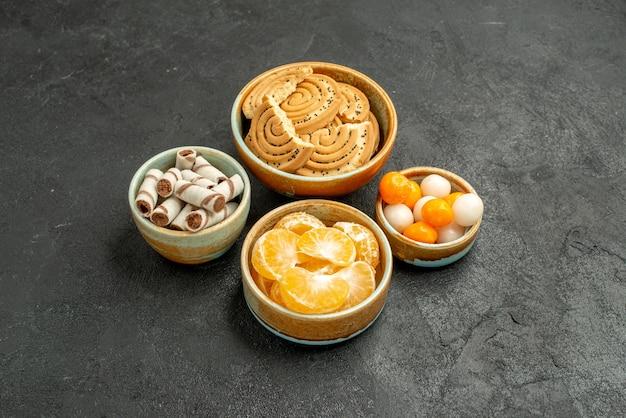 Widok z przodu słodkie ciasteczka z cukierkami na ciemnoszarym stole ciasteczka biszkoptowe słodkie