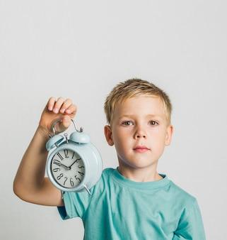 Widok z przodu słodkie dziecko trzyma zegar