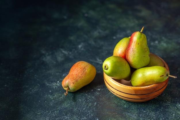Widok z przodu słodkie gruszki na ciemnym tle drzewo dojrzały sok świeży kolor jabłka