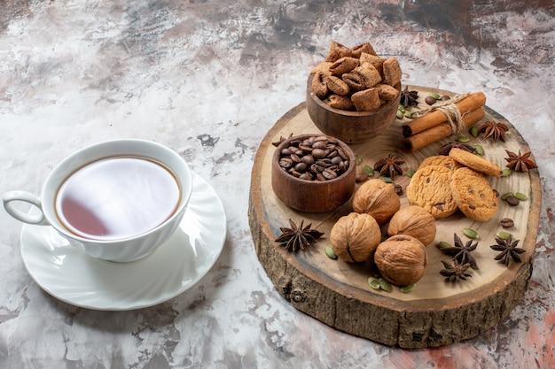 Widok z przodu słodkie herbatniki z filiżanką herbaty i orzechami włoskimi na jasnym tle cukrowe ciastko w kolorze herbaty słodkie ciasto kakaowe
