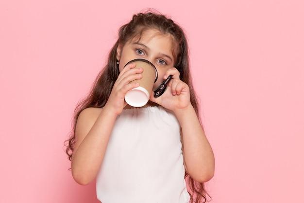 Widok z przodu słodkie małe dziecko pije kawę i rozmawia przez telefon