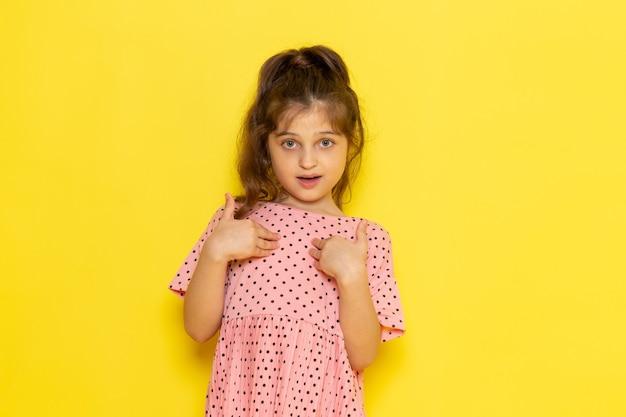 Widok z przodu słodkie małe dziecko w różowej sukience pozowanie