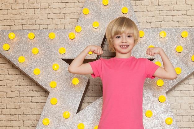 Widok z przodu słodkie małe dziecko w różowych szarych dżinsach z podkoszulkiem na gwiazdowym żółtym stojaku i jasnym tle