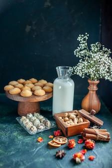 Widok z przodu słodkie pyszne ciasteczka z mlekiem i orzechami na ciemnoniebieskiej powierzchni