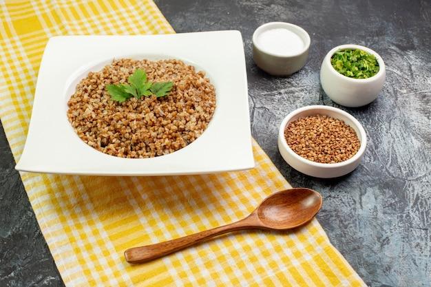 Widok z przodu smaczna gotowana kasza gryczana wewnątrz białego talerza z zielenią na jasnoszarym tle kolor danie jedzenie zdjęcie fasola kaloryczny posiłek