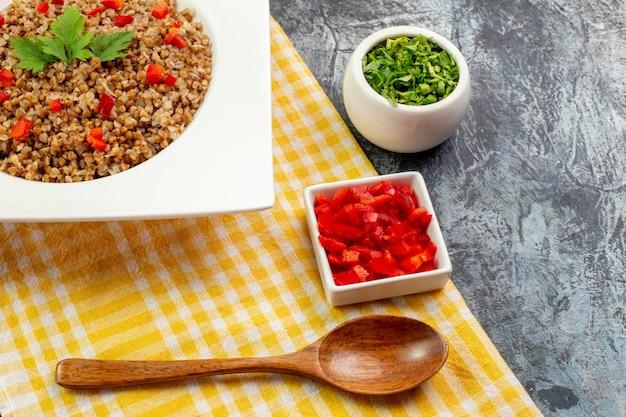 Widok z przodu smaczna gotowana kasza gryczana wewnątrz talerza z zieleniną na jasnoszarym tle kolor danie zdjęcie jedzenie fasola mączka kaloryczna
