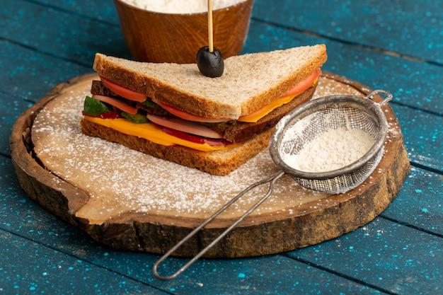 Widok z przodu smaczna kanapka tostowa z szynką serową w środku wraz z mąką na niebiesko