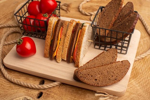 Widok z przodu smaczna kanapka tostowa z szynką serową wraz z bochenkami chleba z czerwonymi pomidorami na drewnianym biurku