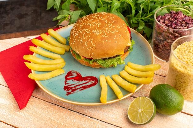 Widok z przodu smaczna kanapka z kurczakiem z zieloną sałatą i warzywami wewnątrz talerza z frytkami na drewnianym biurku z kremem.
