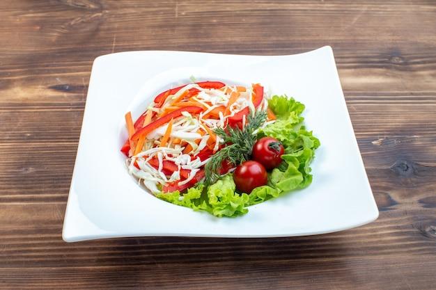 Widok z przodu smaczna sałatka jarzynowa z zieloną sałatą i kapustą wewnątrz talerza na brązowej powierzchni