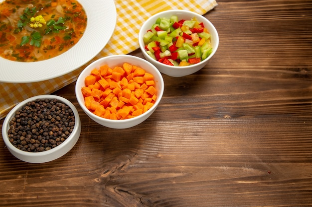 Widok z przodu smaczna zupa jarzynowa z pokrojonymi warzywami na brązowym drewnianym biurku
