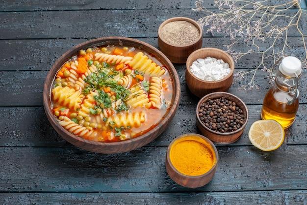 Widok z przodu smaczna zupa makaronowa ze spiralnego makaronu z przyprawami na ciemnoniebieskim daniu z sosem na biurko włoska zupa makaronowa