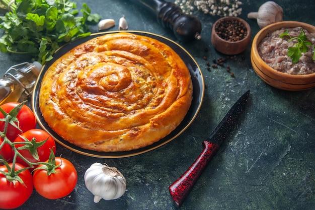 Widok z przodu smaczne ciasto mięsne wewnątrz patelni z pomidorami na ciemnym tle ciasto jedzenie piec ciasto piekarnik ciasto ciasto herbatniki