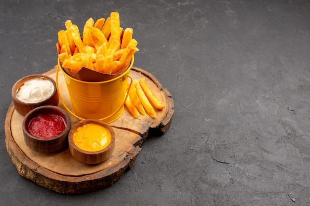 Widok z przodu smaczne frytki z sosami na ciemnej przestrzeni