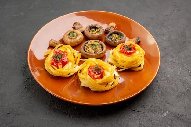 Widok z przodu smaczne gotowane grzyby z makaronem ciasta na ciemnym stole obiad posiłek