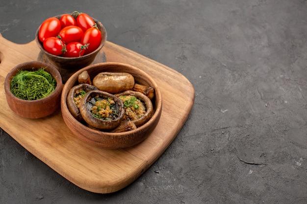 Widok z przodu smaczne gotowane grzyby z pomidorami na ciemnym stole dojrzałe dzikie jedzenie