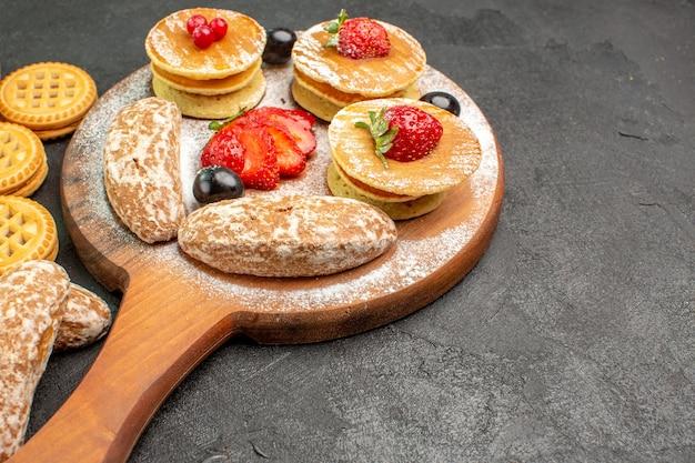 Widok z przodu smaczne naleśniki ze słodkimi ciastami i owocami na ciemnej powierzchni słodki deser ciasta