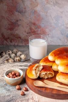 Widok z przodu smaczne pieczone ciepłe bułeczki ze szklanką mleka