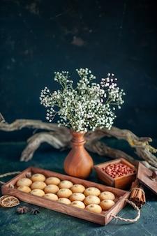 Widok z przodu smaczne słodkie herbatniki z orzeszkami ziemnymi na ciemnej powierzchni