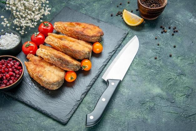 Widok z przodu smaczne smażone ryby z pomidorami na ciemnoniebieskiej powierzchni owoce morza sałatka posiłek mięso owoce morza gotowanie smażone danie
