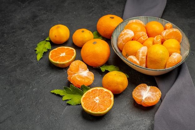 Widok z przodu smaczne soczyste mandarynki na ciemnym tle kolor kwaśne egzotyczne zdjęcie pomarańczowe owoce cytrusowe