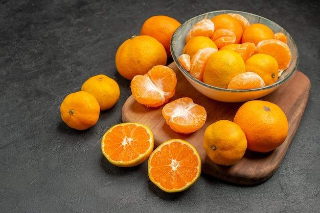 Widok z przodu smaczne soczyste mandarynki wewnątrz talerza na szarym tle egzotyczne owoce cytrusowe kolor zdjęcia kwaśna pomarańcza