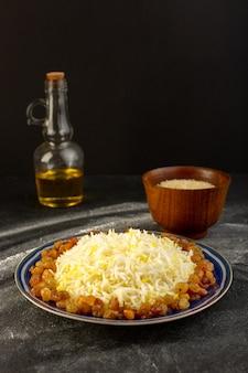Widok z przodu smacznego pilawu z oliwą i suszonymi rodzynkami wewnątrz talerza na ciemnej powierzchni