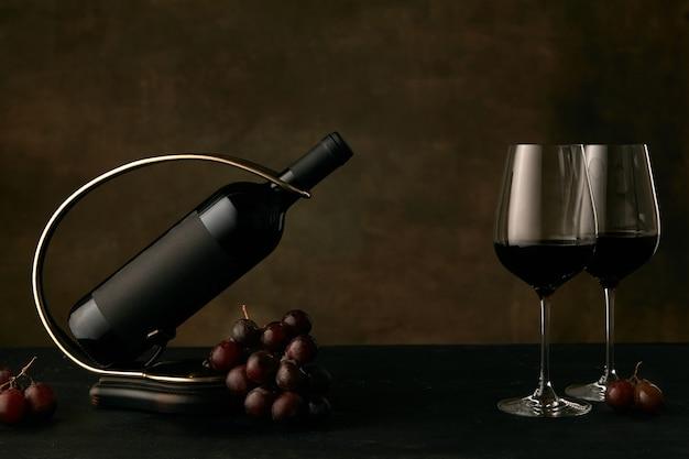 Widok z przodu smacznego talerza z winogronami z butelką wina na ciemnym tle studyjnym
