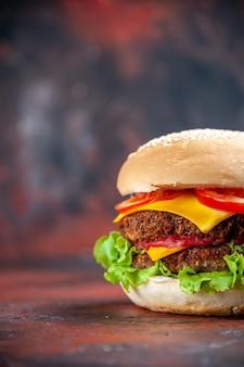 Widok z przodu smaczny burger mięsny z serem i sałatką na ciemnym tle